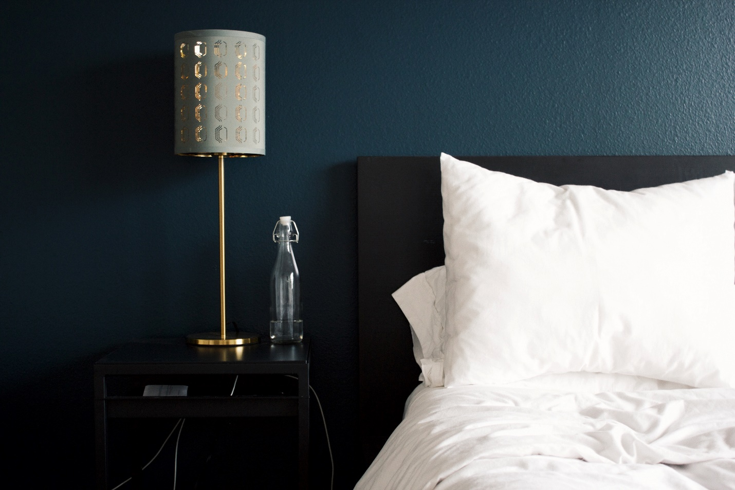 A hotel room bed and nightstand.