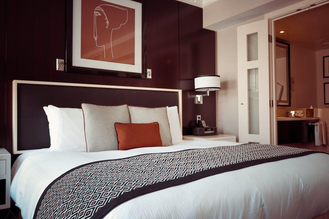 A posh hotel room with a black and white bedspread and painting