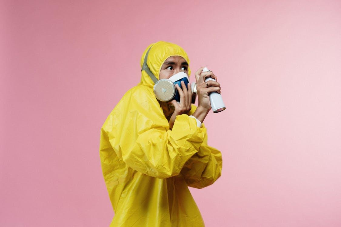Man in yellow PPE and a gas mask holding an aerosol spray up.