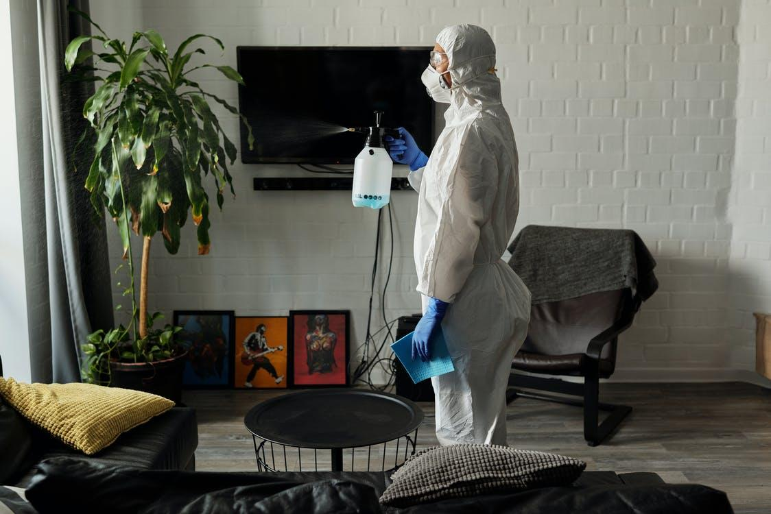 An exterminator spraying insecticide in a home.