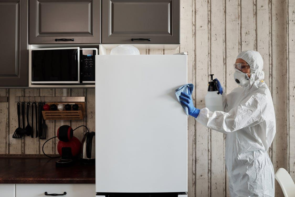 Person in PPE wipes down a fridge