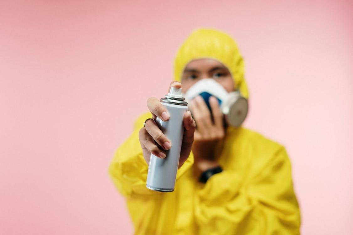 a pest exterminator in yellow PPE showing a spray bottle to the camera
