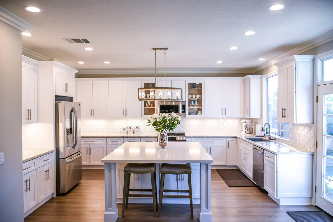 a clean kitchen with white furniture
